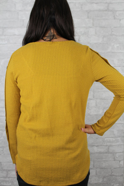 Back side of mustard waffle knit sweater with button sleeves.