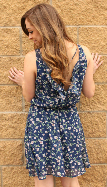 Light navy floral print dress with an elastic waist and a ruffle v-neck back.