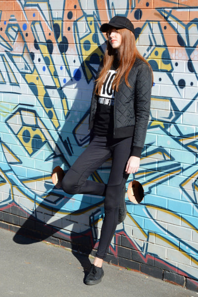 tall-woman-wearing-activewear-black-bomber-jacket-and-cap