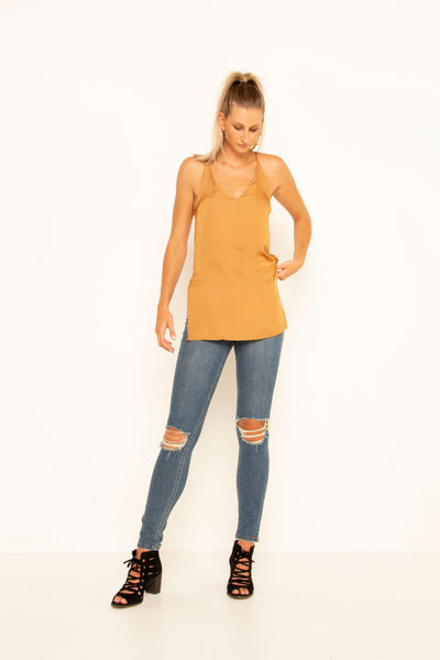 tall-mustard-silky-top-front-hand-on-hip-looking-down-v-neck-sleeveless-side-slits