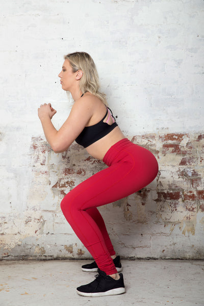 tall-woman-squats-in-red-leggings
