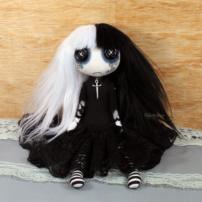A cute, button eyed, Goth girl art doll, dressed in black lace, with half and half, black and white hair, and a sword necklace.