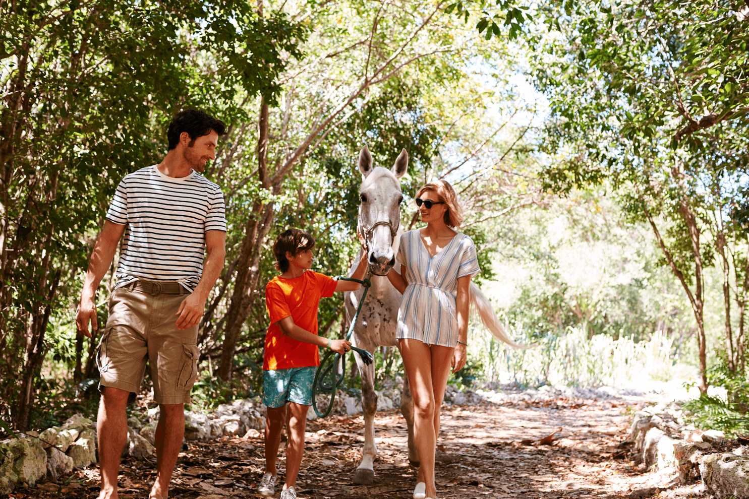 A family with a horse near the beach in Punta Cana styled by Sarah Parlow Fashion Stylist.