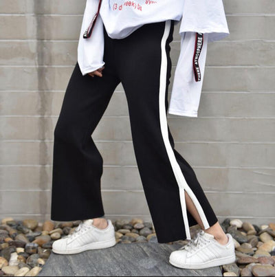 Woman wearing black and white pants with white sneakers and a white top standing on a slab on top of stones