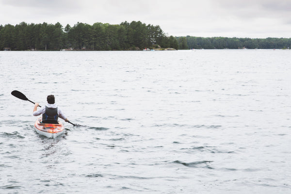 man paddling kayak across lake or river