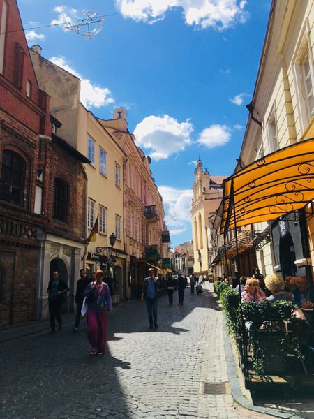 Indre strolling the quaint old town streets of Vilnius in Lithuania wearing linen pants