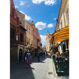 Indre walking downt he street in Vilnius, Lithuania, wearing fuchsia linen pants