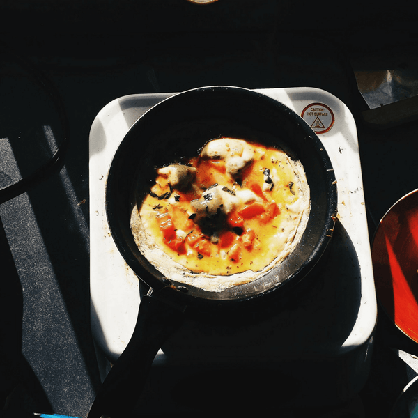 Omelette in a black frying pan on a white single stove burner