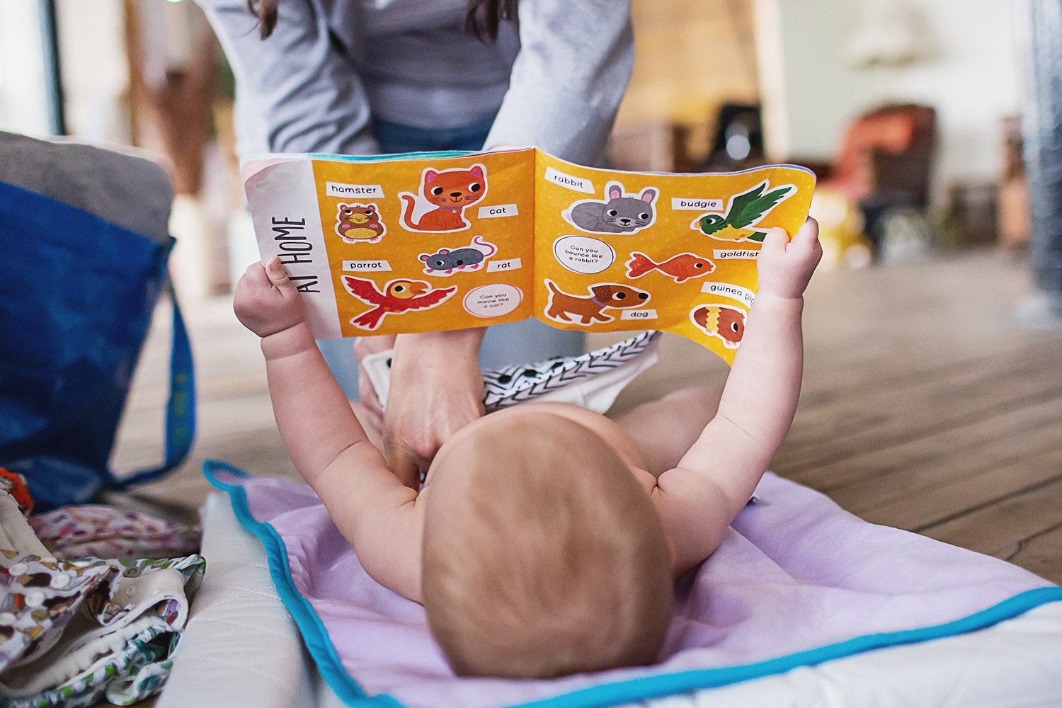 Baby reading while having nappy changed