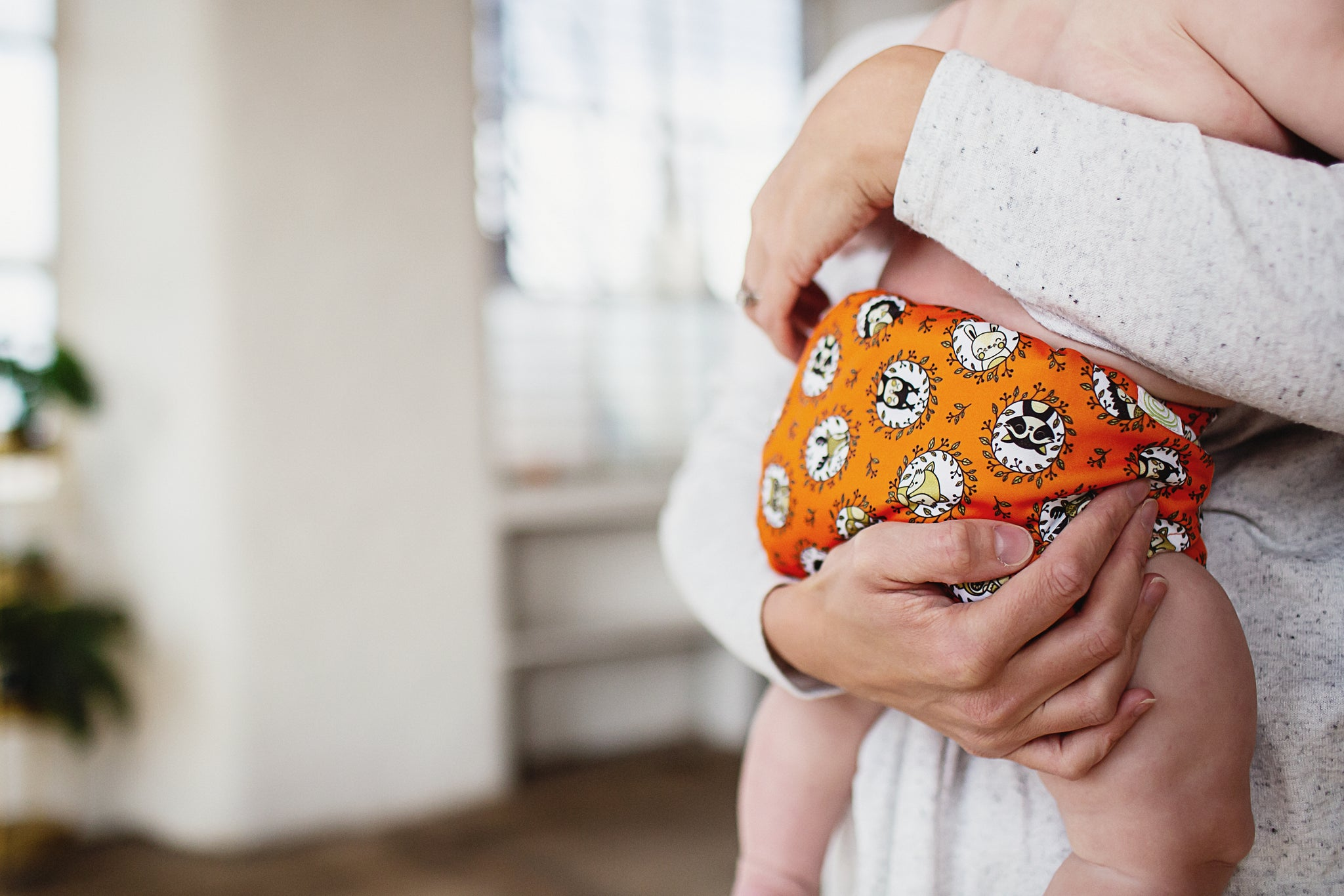 Parent holding baby in orange reusable nappy