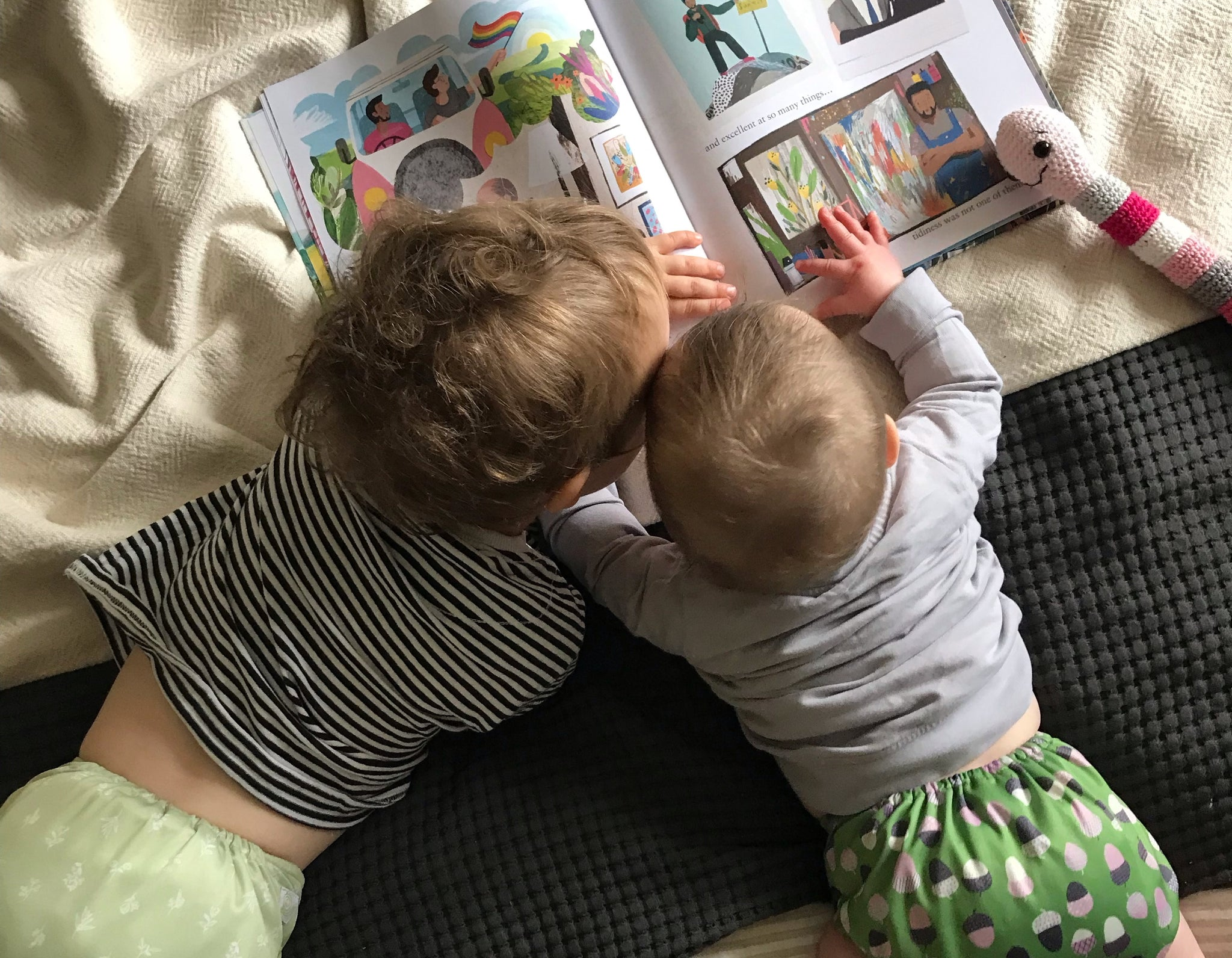 Two babies lay down reading a book