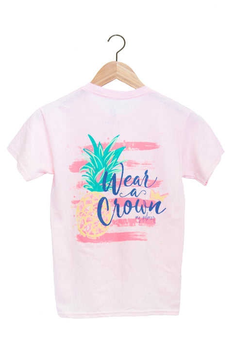 "Youth light pink short sleeve shirt with pineapple graphics and the words ""wear a crown."""