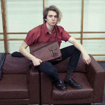 Model with brown vintage leather messenger bag