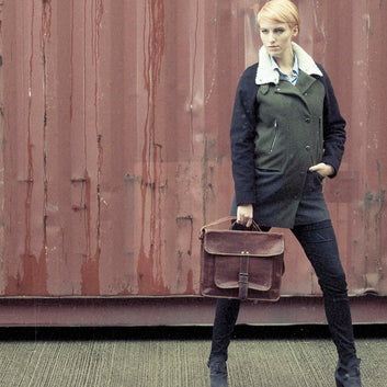 Model with brown vintage leather satchel