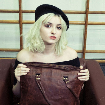 Model with brown vintage leather tote bag