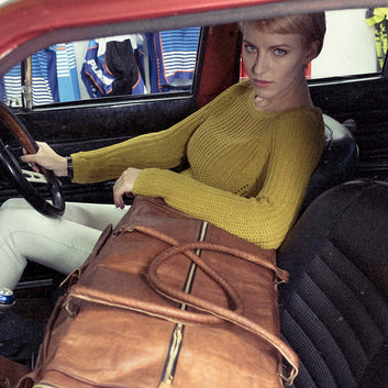 model with vintage leather travel bag