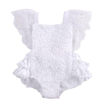 Baby Girl Romper all white lace with a tiered ruffled bottom and adorned with a pink bow on the back, lace flutter sleeves drape loosely over babies shoulders.