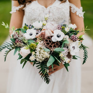 Bridal bouquet with anemones, lotus pods, blush peonies, ferns, and eucalyptus
