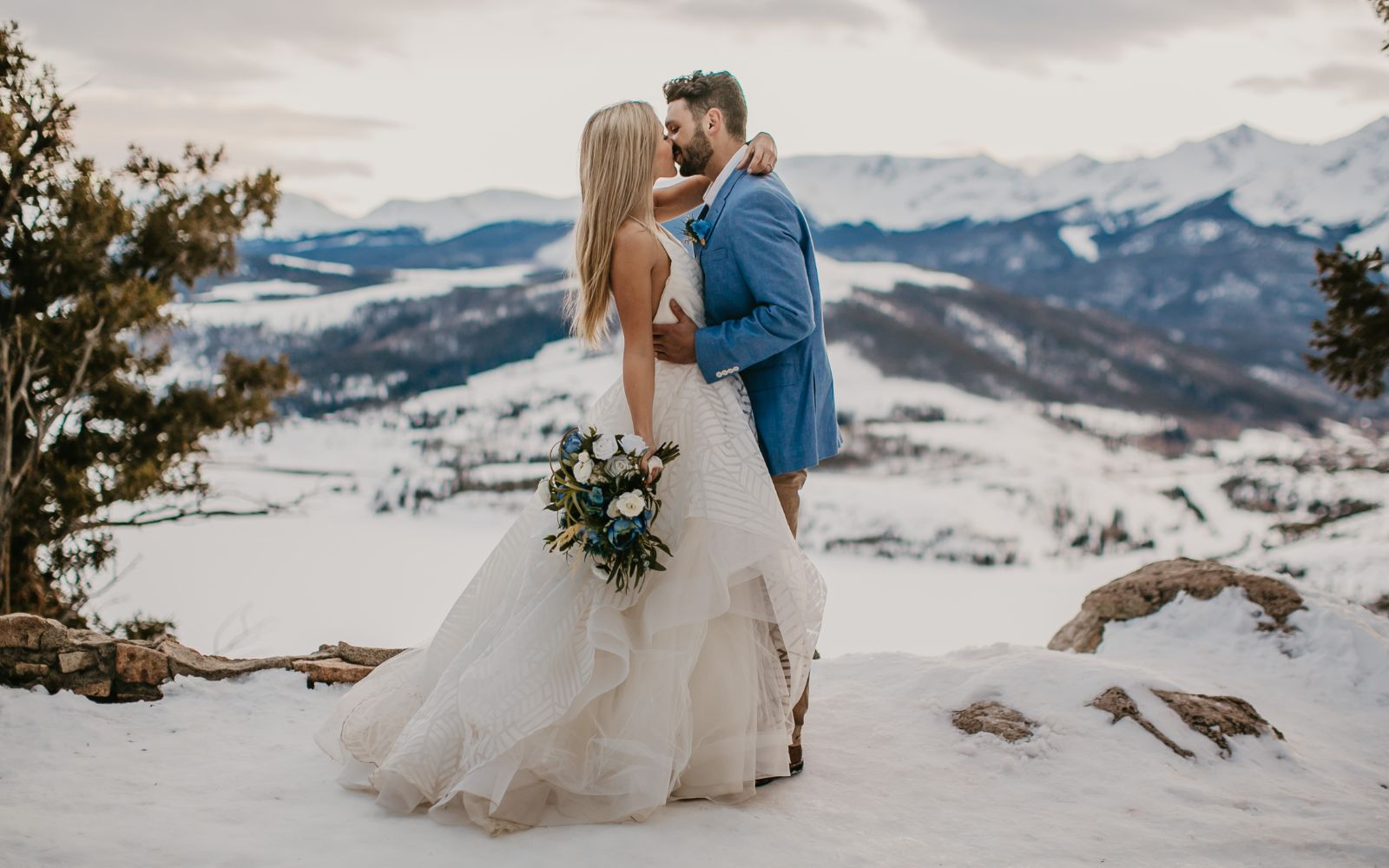 Bride and Groom kissing in front of the snowy Rocky Mountains. The bride is holding a blue and white bridal bouquet with lots of greenery.