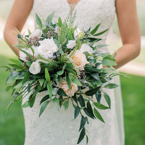 A bridal bouquet overflowing with greenery and blush roses, white lisianthus, and mauve berries. Compass Rose Floral can create any shape, size, or color combination for your perfect bridal bouquet!