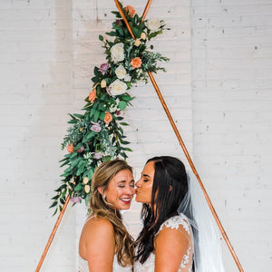 Two brides standing underneath a copper triangle arch adorned with an arch swag that combined the flowers that were in each bride's bouquet. Orange and lavender roses with greenery.