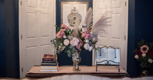 A funeral flower arrangement made of dusty pink peonies, blush cabbage roses, and pampas grass