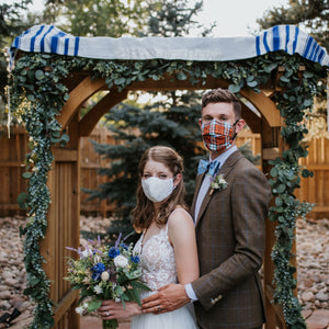 A bride and groom wearing masks stand in front of their wedding arbor while the bride holds her wildflower bouquet with blue cornflower, white ranunculus, and lots of texture. The groom's boutonniere has lavender and greenery.