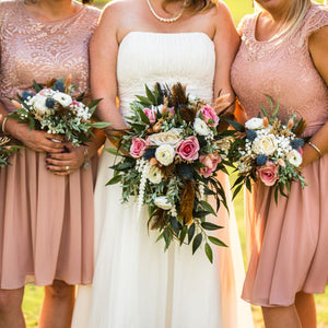 Unique wedding bouquets made with dusty rose roses, blue thistle, and brown feathers