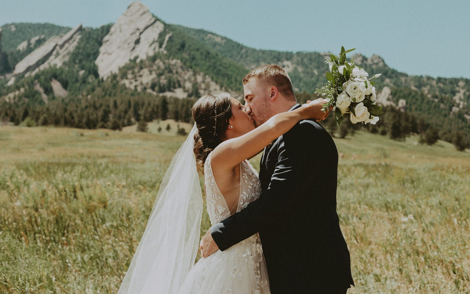 A bride and groom kiss in front of the Boulder flatirons, the bride is holding a bouquet made out of white roses, white ranunculus, sweet pea, and beautiful greenery.
