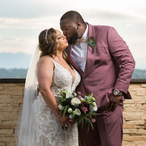 A groom kisses his bride while wearing a dusty rose suit, and his bride is holding a matching bridal bouquet of roses, ranunculus, and greenery.