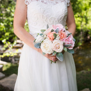A bride holds her traditional bridal bouquet made of cabbage roses, peach roses, pink roses, and lamb's ear