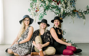 The employees of Compass Rose Floral sit in the Sugar Hill Studio in front of the floral tree they created. The tree has rust orange peonies, blue tweedia, white wisteria, and magenta roses. Photo taken by Sarah Hill Photography
