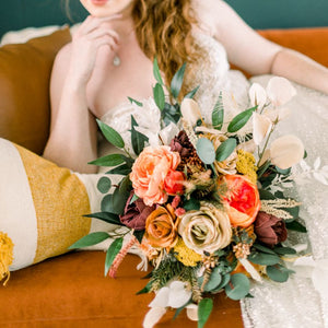 Boho bridal bouquet with rust orange roses, magenta peonies, beige ranunculus, feathers, and greenery