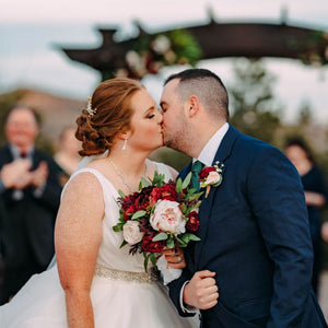 A bride and groom kiss in front of Willow Ridge Manor's arbor, the bride is holding her burgundy and blush bridal bouquet