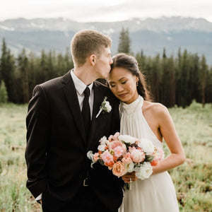 A couple who has just eloped in the Rocky Mountains embraces. The groom has a white boutonniere on his black suit, and the bride holds her bouquet of pink peonies, peach tea roses, white garden roses, and sweet pea made for her by Compass Rose Floral