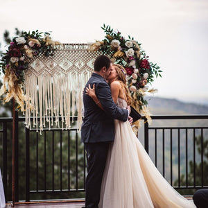 A couple shares their first kiss as husband and wife in front of a rectangular copper arch with macrame and two arch swags with boho inspired flowers and lots of feathers!