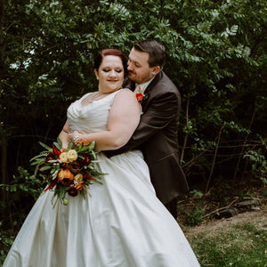 A bride and groom embrace while the bride holds her fall inspired bouquet made of ferns, yellow ranunculus, and terracotta peonies