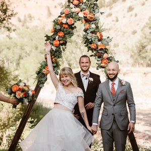 A couple who has just gotten married stands in front of their wooden triangle arch adorned with orange roses, peonies, lotus pods, and greenery. Compass Rose Floral can create the perfect arch flowers for the wedding of your dreams!