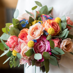 A very colorful bouquet made with coral peonies, pink roses, peach tea roses, and eucalyptus