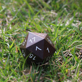 Extra large ebony wooden d20 on grass