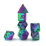 Stacked purple, blue and green plastic dice set.