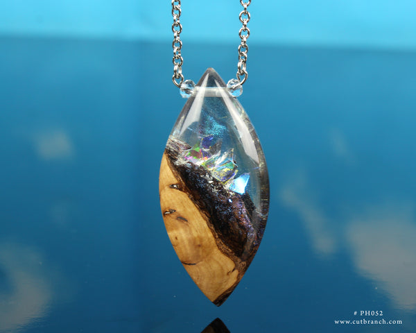 rainbow reflections within a resin and wood necklace pendant, handmade