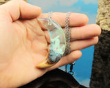 cut branch resin and wood crescent moon pendant held in hand
