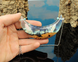 resin and wood statement moon pendant being held in hand