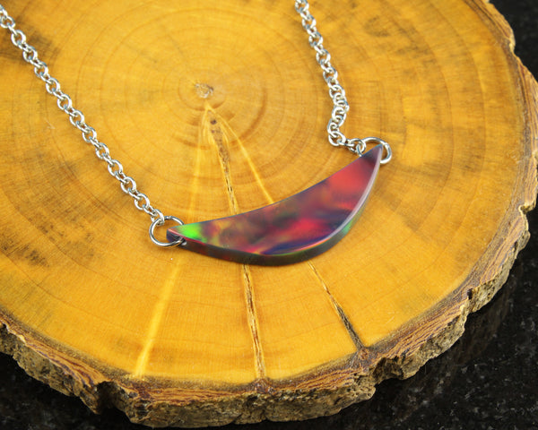red aurora opal moon pendant necklace on wood background