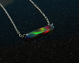 Red aurora opal bar necklace showing rainbow of colors on black background