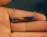 red aurora opal bar necklace by cut branch held in hand