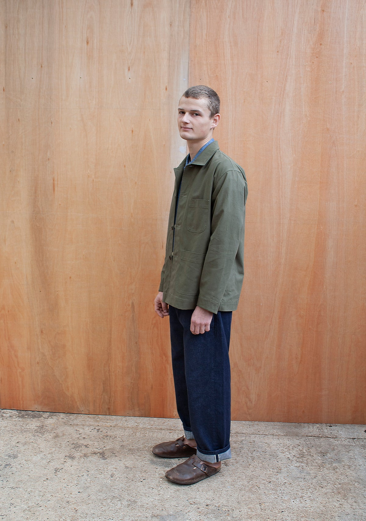 a young man standing against a wooden wall wearing a traditional chore jacket made in a sage green  brushed cotton canvas