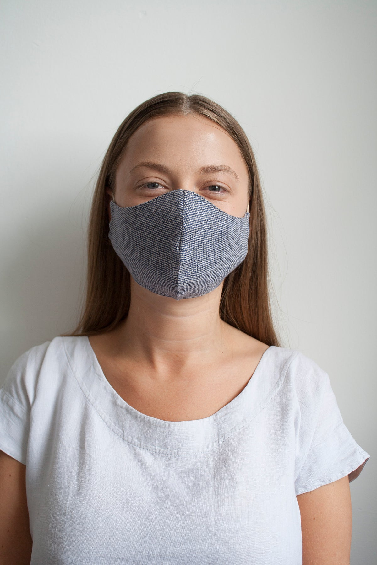 a girl wearing a checked cotton facemask made in the UK