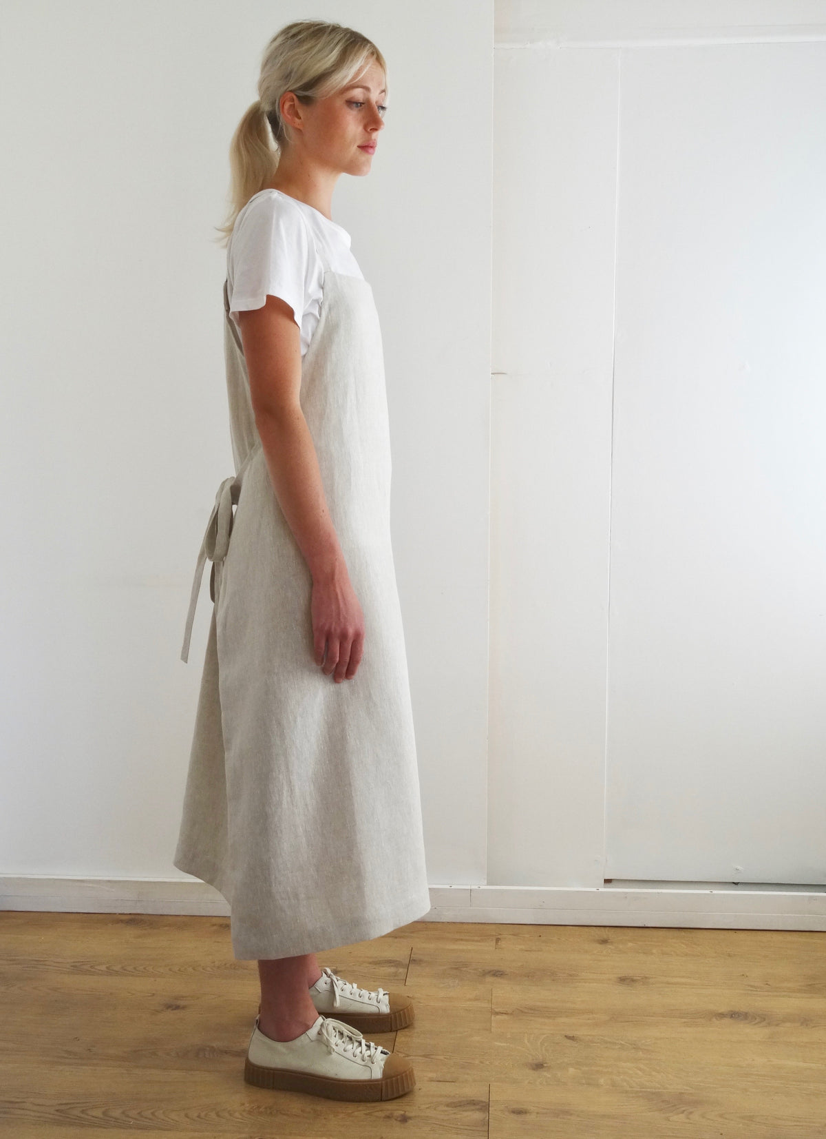 side view of young woman wearing a cream linen apron dress